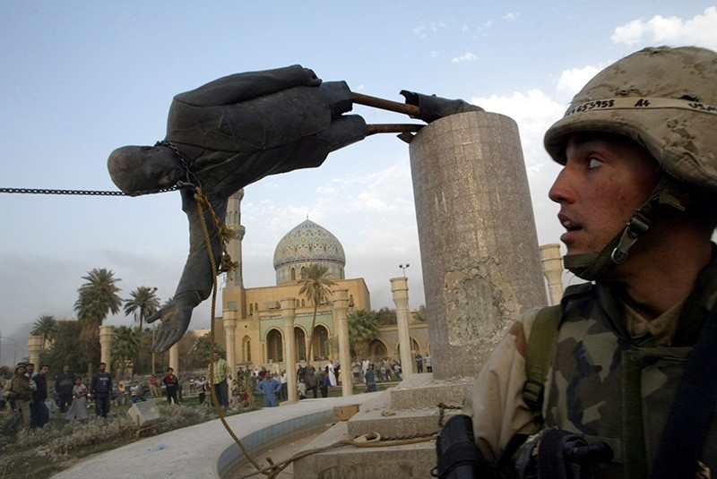 A U.S. soldier watches as a statue of Iraq's President Saddam Hussein falls in central Baghdad, Iraq April 9, 2003. (Reuters Photo)
