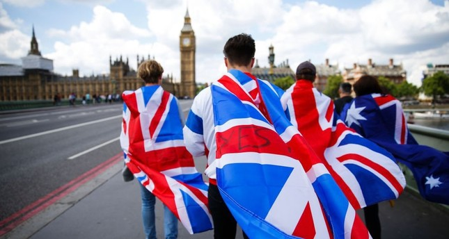 People walk over Westminster Bridge wrapped in Union Jacks, toward Big Ben and the Houses of Parliament in central London, June 26.