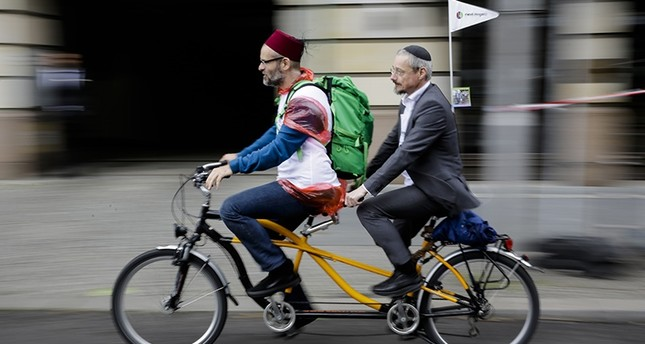 A Muslim and a Jewish man rides a tandem together during a bicycle tandem tour of Jews and Moslems against anti-Semitism and hatred of Muslims in Berlin, Sunday, June 24, 2018. (AP Photo)