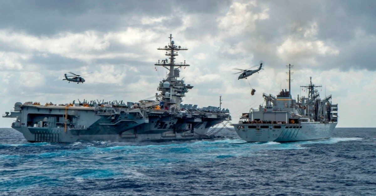 This US Navy handout picture dated May 8, 2019 shows USS Abraham Lincoln aircraft carrier while conducting a replenishment-at-sea with the fast combat support ship USNS Arctic. (Photo by MCSN Jason Waite / Navy Office of Information / AFP)