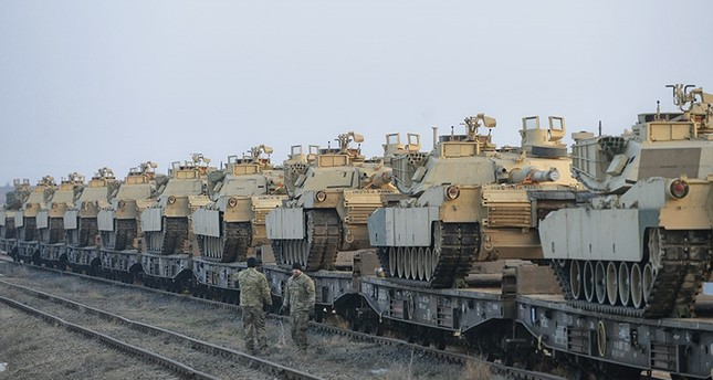 Servicemen of the Fighting Eagles 1st Battalion, 8th Infantry Regiment, walk by tanks that arrived via train to the US base in Mihail Kogalniceanu, eastern Romania, Tuesday, Feb. 14, 2017. (AP Photo)