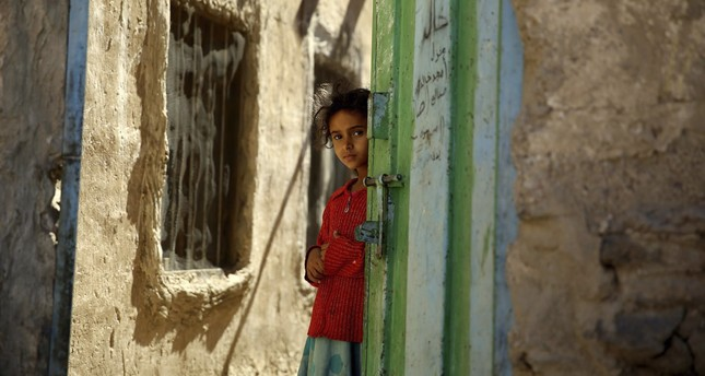A Yemeni girl stands in a doorway in the conflict zone in Sanaa, Yemen, Nov. 9, 2015.