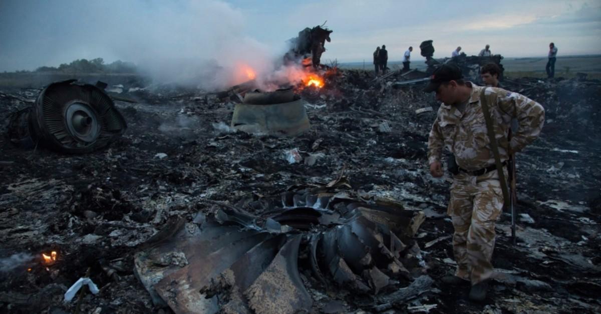 People walk amongst the debris at the crash site of a passenger plane near the village of Grabovo, Ukraine, Thursday, July 17, 2014. (AP Photo)