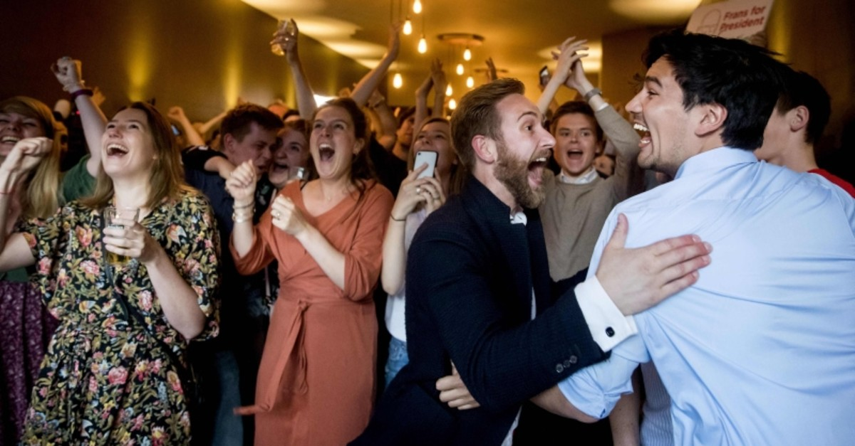Members of the Labour Party (PvdA) of Frans Timmermans celebrate after the exit polls of the European Parliament elections in cafe Millers on May 23, 2019 in The Hague. (Photo by Koen van Weel / ANP / AFP)