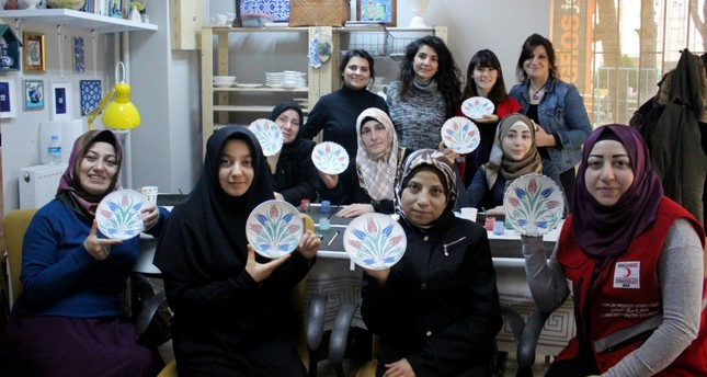 Syrian and Turkish women at the community center pose at a class of plate painting.