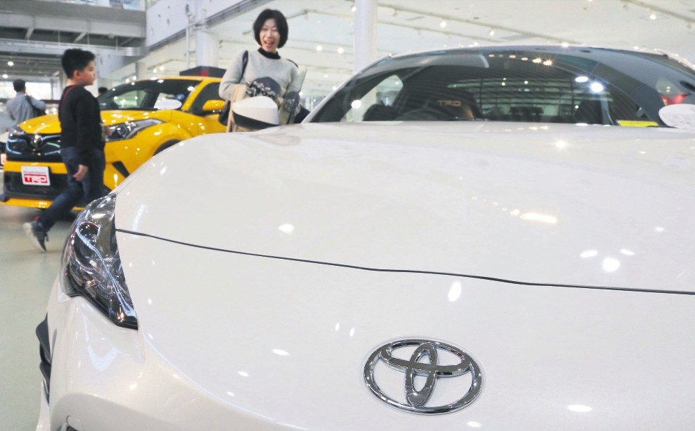 Visitors take a look at a Toyota car at its showroom in Tokyo. Toyota plans to offer more than 10 purely electric vehicle models in its lineup by the early 2020s, marking the Japanese automaker's commitment to that growing technology sector.