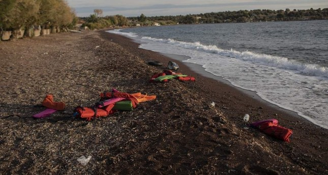 Life vests are seen on a beach at the seaside village of Tsonia, Lesbos island, Greece after the arrival of refugees and migrants on a rubber boat from Turkey, Oct. 7, 2019. (AP Photo / Petros Giannakouris)