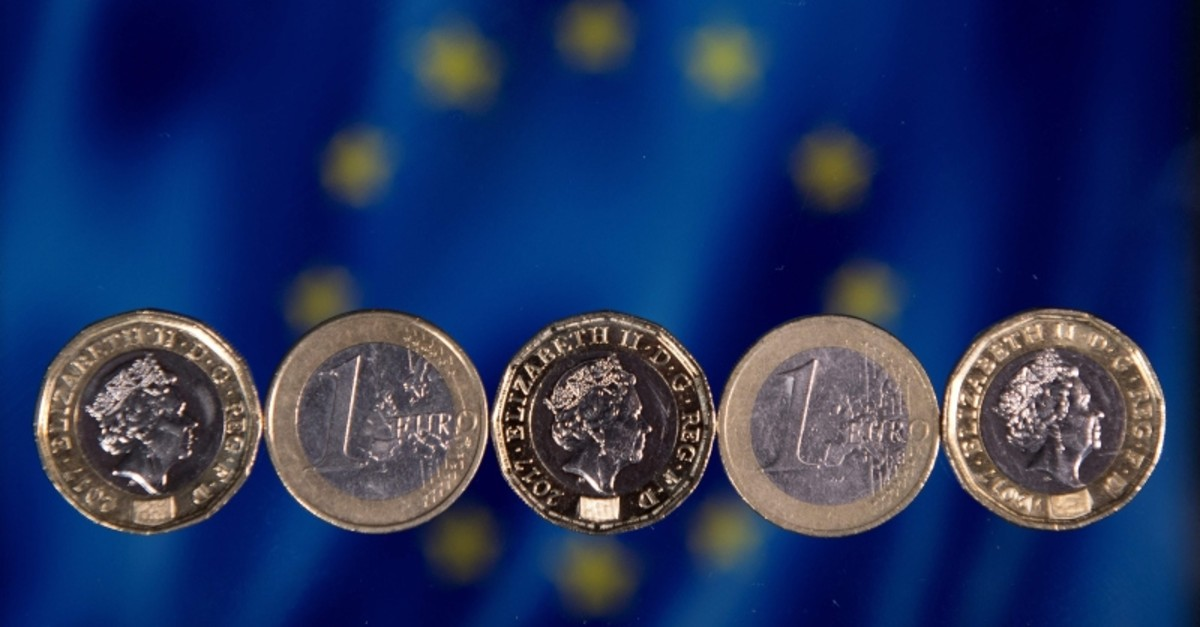 In this file photo taken on December 14, 2017 British one pound sterling coins and two Euro coins are arranged in front of the European Union flag in a photograph in London. (AFP Photo)