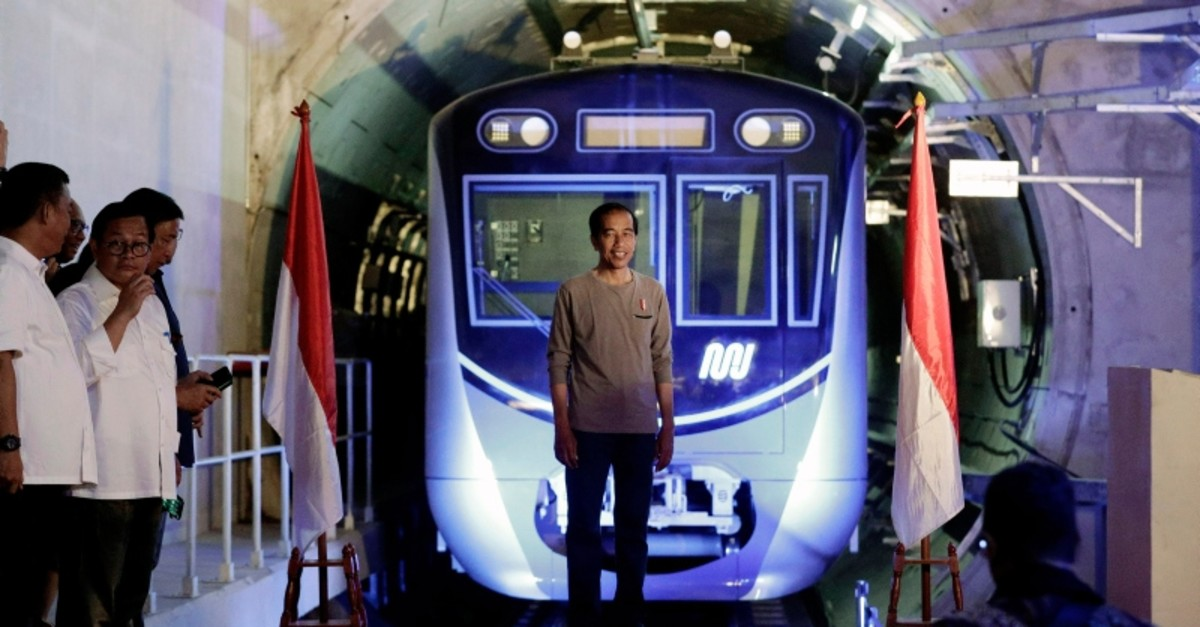 Indonesian President Joko u201cJokowiu201d Widodo, center, stands on a stage with the background of a Jakarta Mass Rapid Transit train during the inauguration ceremony of the subway line in Jakarta, Indonesia, Sunday, March 24, 2019 (AP Photo)