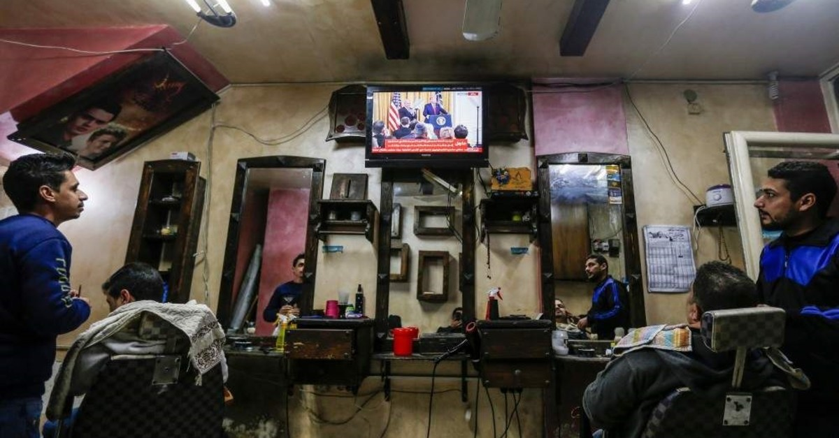 Palestinians watch the televised press conference of U.S. President Donald Trump and Israeli Prime Minister Benjamin Netanyahu at a barber shop in Gaza City, Jan. 28, 2020. (AFP Photo)