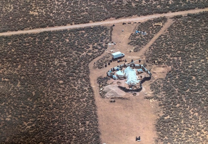 This Friday, Aug. 3, 2018, aerial photo released by Taos County Sheriff's Office shows a rural compound during an unsuccessful search for a missing 3-year-old boy in Amalia, N.M. (Taos County Sheriff's Office via AP)