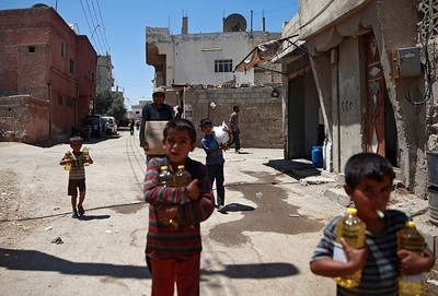 Syrian children and a man are seen carrying food aid in Douma, near Damascus, Syria August 6, 2017 (Reuters Photo)