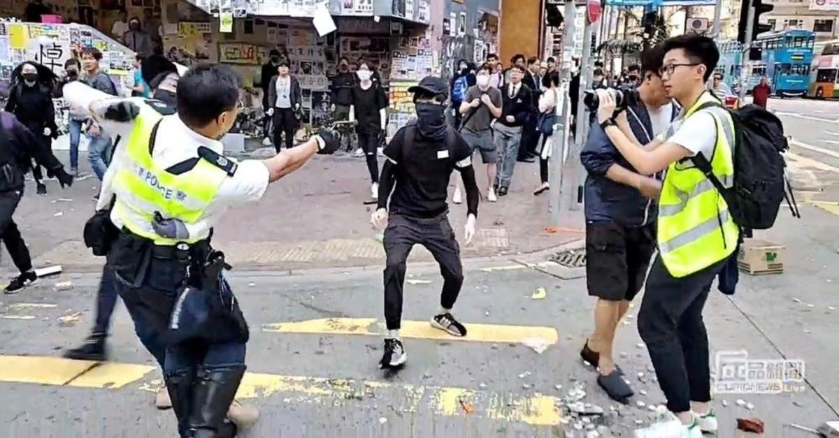 A still image from a social media video shows a police officer aiming his gun at a protester in Sai Wan Ho, Hong Kong, Nov. 11, 2019. (Cupid Producer via Reuters)