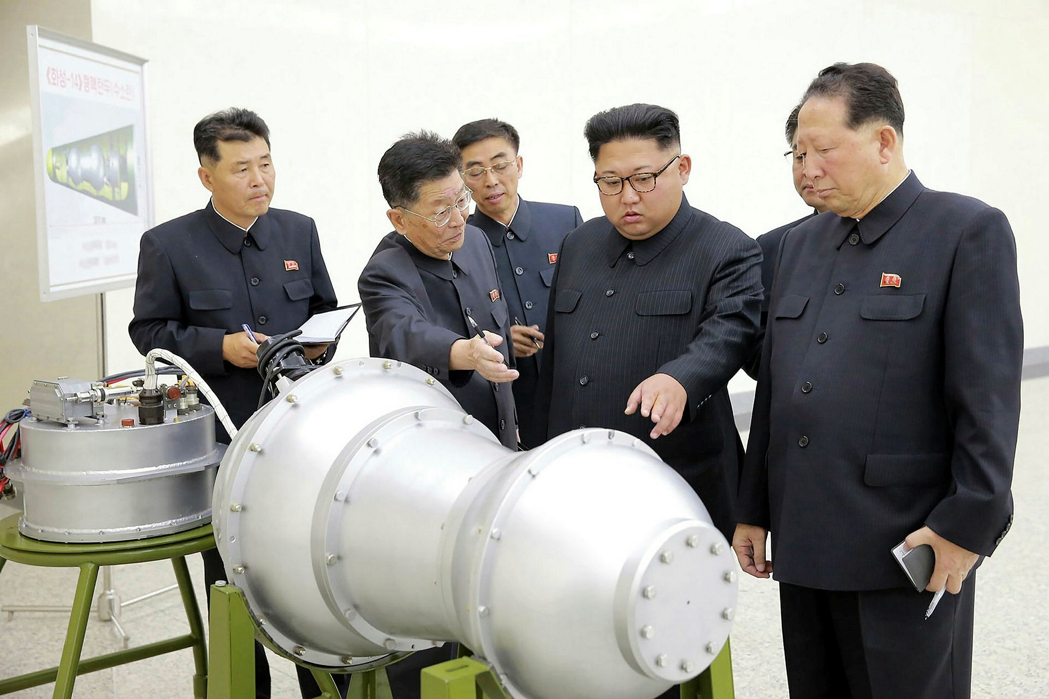 This undated picture released by North Korea's official Korean Central News Agency (KCNA) on September 3, shows North Korean leader Kim Jong-Un (C) looking at a machine resembling a rocket engine at an undisclosed location.