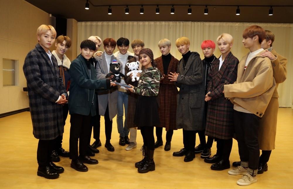 Havin Ayu015fe Baldaz (center) poses with members of K-Pop band Seventeen.