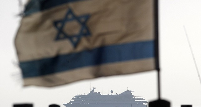 An Israeli flag flutters in the wind as a naval vessel not seen escorts the Mavi Marmara that was raided by Israeli marines, to the Ashdod port, in this May 31, 2010 file picture. Reuters