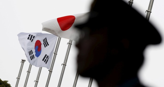 A police officer stands guard near Japan and South Korea national flags at a hotel in Tokyo June 22, 2015. (REUTERS Photo)