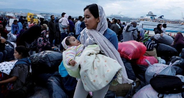 A woman holds her baby as refugees and migrants arrive on a passenger ferry from the island of Lesbos at the port of Piraeus, Oct. 7, 2019. Reuters Photo