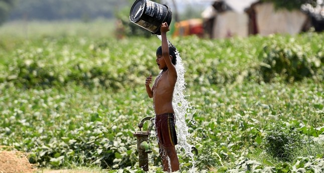In this file photo taken on May 29, 2019, an Indian boy pours water on himself as he tries to cool himself off amid rising temperatures in New Delhi. (AFP Photo)