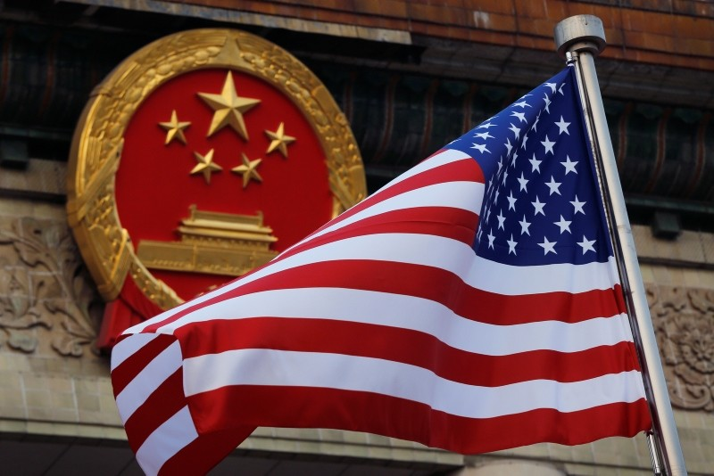 In this Nov. 9, 2017, file photo, an American flag is flown next to the Chinese national emblem during a welcome ceremony for visiting U.S. President Donald Trump. (AP Photo)