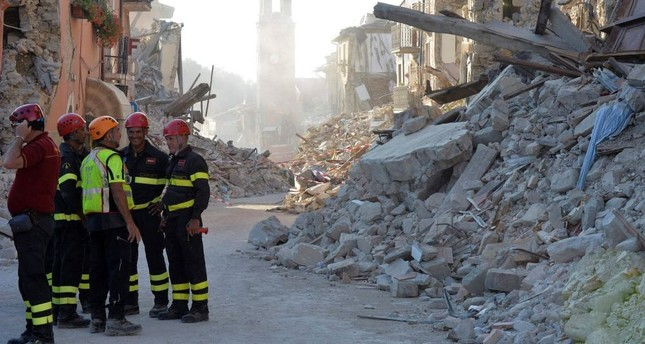 Firefighters and rescue workers stand near the damaged Sant'Agostino church (C) and rubble and debris of damaged buildings.