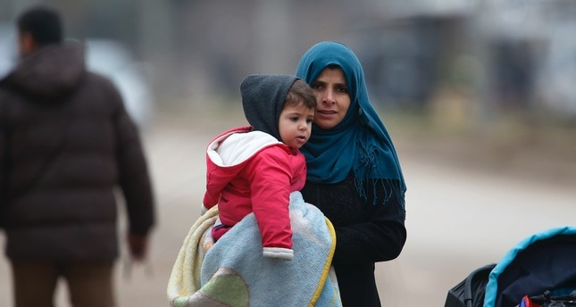 A Syrian woman holding a child walks towards Syria from Turkey at the Öncüpınar border crossing with Syria, Kilis, Turkey, Jan. 26. 2018.