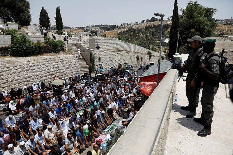 Israeli border police officers stand guard as Palestinians pray at Lions' Gate, the entrance to Jerusalem's Old City, in protest over Israel's new security measures at the compound housing al-Aqsa mosque on July 20, 2017. (Reuters Photo)