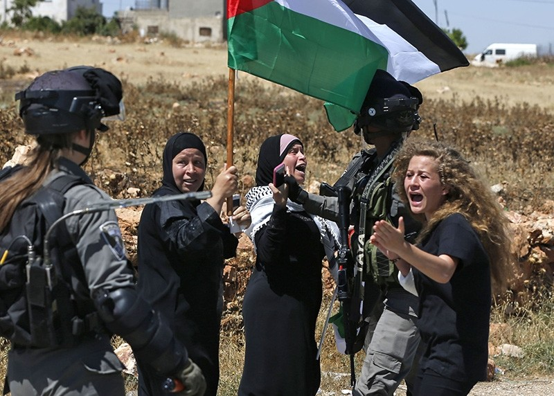 In this file photo taken on May 26, 2017 Palestinian Ahed Tamimi (R) reacts in front of Israeli forces during a demonstration on May 26, 2017, in the village of Nabi Saleh, north of Ramallah, in the Israeli-occupied West Bank. (AFP Photo)