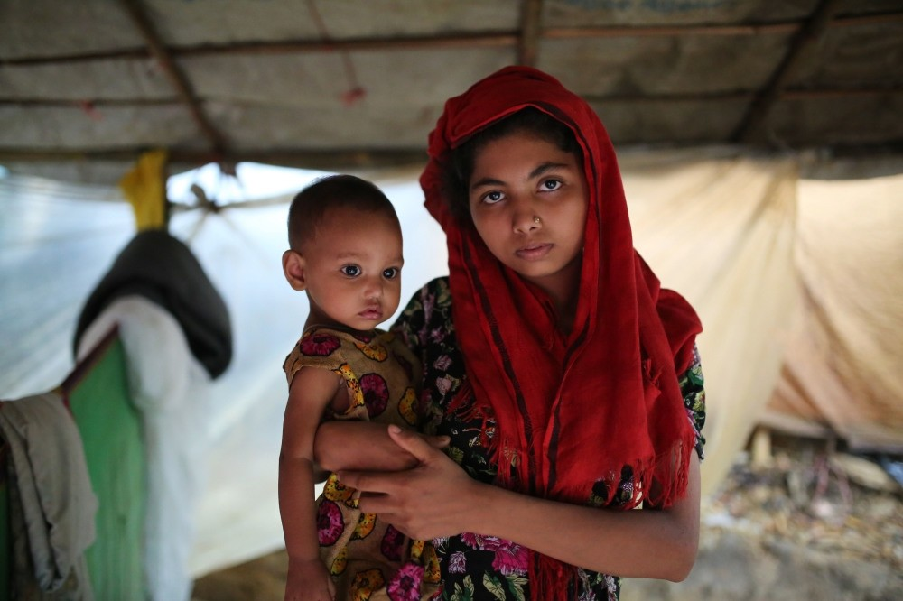 A Rohingya woman holds her child and stands for a photograph at a makeshift camp near the Kutupalong refugee camp in Cox's Bazar, Bangladesh, Oct. 3.
