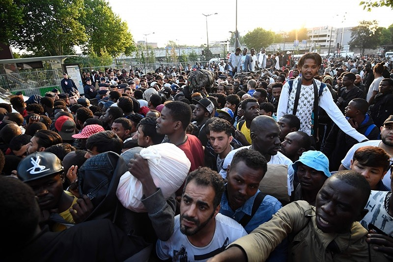 French anti-riot police CRS officers surround migrants and refugees during the evacuation of a makeshift camp at Porte de la Chapelle, northern in Paris, on July 7, 2017, one of several camps sprouting up around the French capital. (AFP Photo)