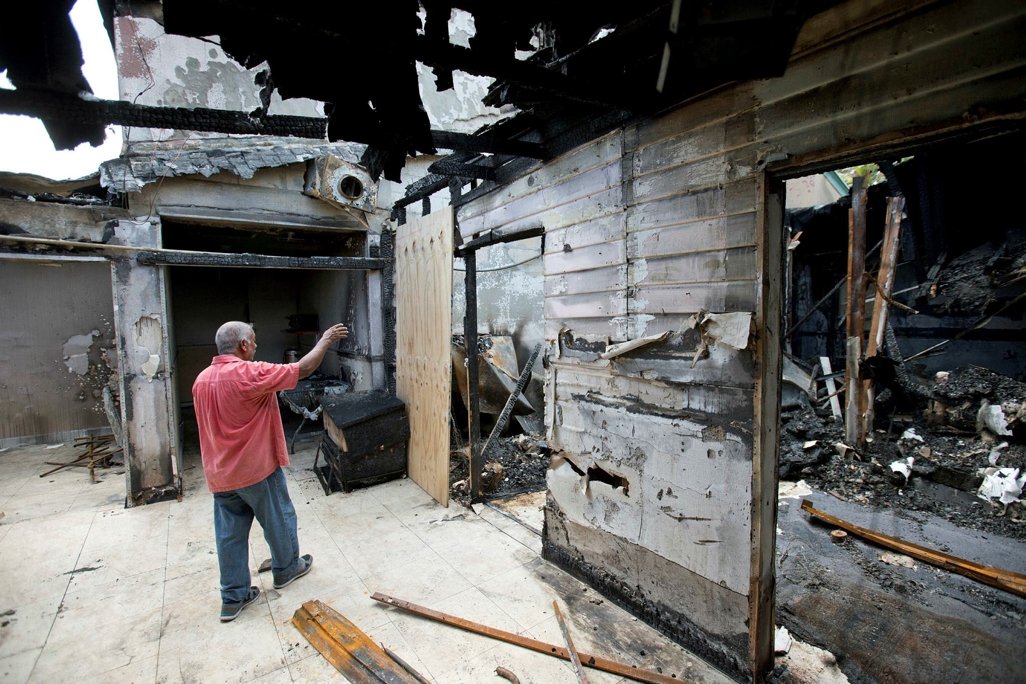 Farhad Khan, who has attended the Islamic Center of FortPierce for more than seven years, shows members of the media its charred remains, in Fort Pierce, Fla. (AP Photo)