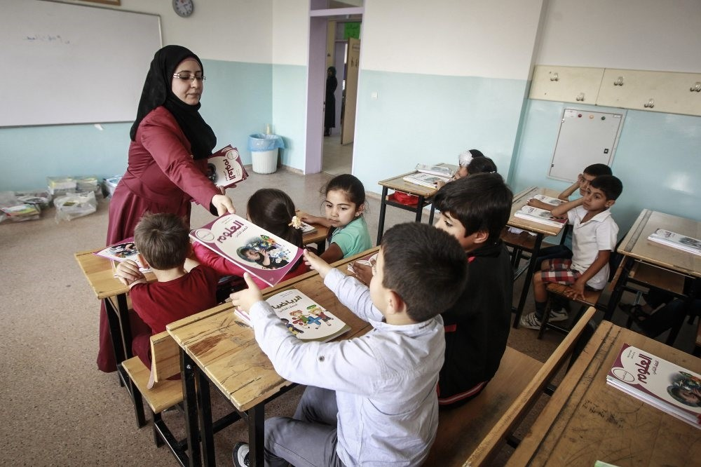 A teacher distributes textbooks to Syrian students at a school in the capital Ankara.