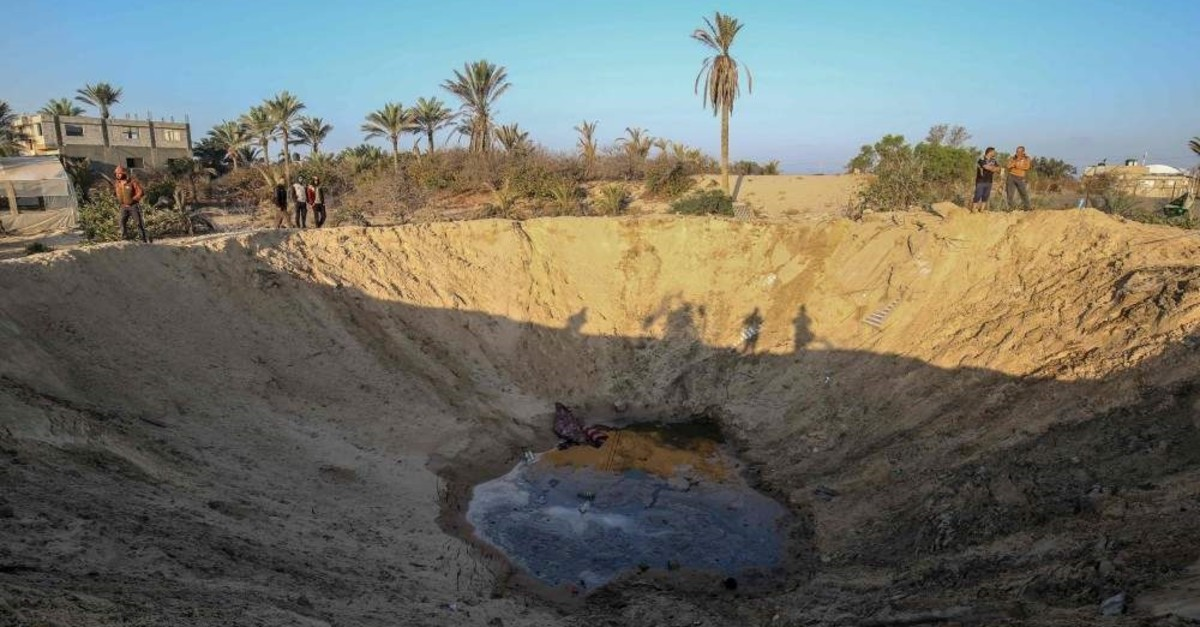 Palestinian men walk around a crater caused by an Israeli airstrike launched in response to rocket fire, in Khan Yunis in the southern Gaza Strip on November 2, 2019. (AFP Photo)