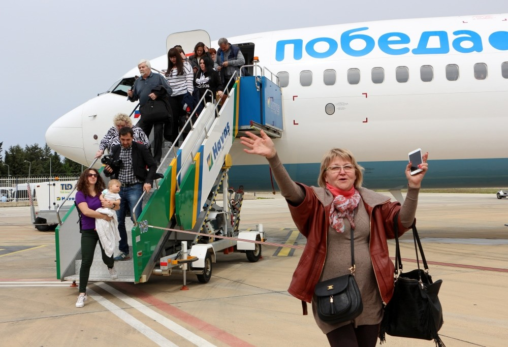 A Russian woman waves as her flight arrives Antalya. Russian Deputy Prime Minister Dvorkovich announced that they withdraw the warning against charter flights to Turkey. The statement came after Erdou011fan and Putin met in Sochi on Wednesday.