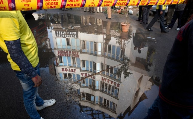 The Arpit Palace Hotel is reflected in a puddle after an early morning fire at the hotel killed more than a dozen people in the Karol Bagh neighborhood of New Delhi, India, Tuesday, Feb.12, 2019. (AP Photo)