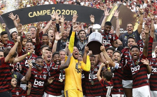 Players from Brazil's Flamengo celebrate on the podium with the trophy after winning the Copa Libertadores final football match by defeating Argentina's River Plate, at the Monumental stadium in Lima, on November 23, 2019. AFP Photo