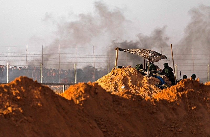 Israeli snipers watch Palestinian demonstrators on the Israeli border with the southern Gaza Strip as smoke billows from tyres burnt by Palestinians. (AFP Photo)