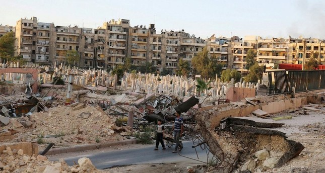 People walk near an over-crowded graveyard in the opposition-held al-Shaar neighborhood of Aleppo, Syria Oct. 6.