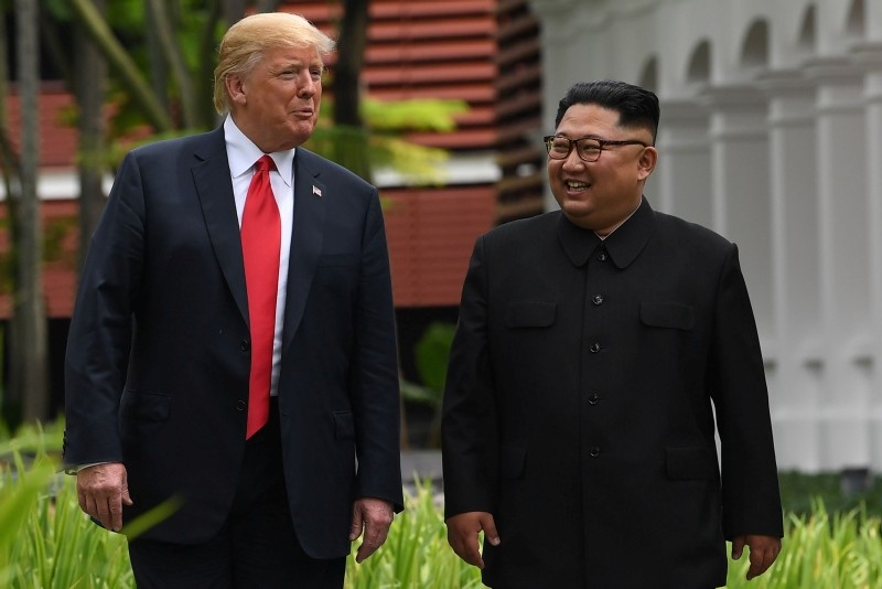 In this file photo taken on June 11, 2018 North Korea's leader Kim Jong Un (R) walks with US President Donald Trump (L) during a break in talks at their historic US-North Korea summit, at the Capella Hotel on Sentosa island in Singapore. (AFP Photo)