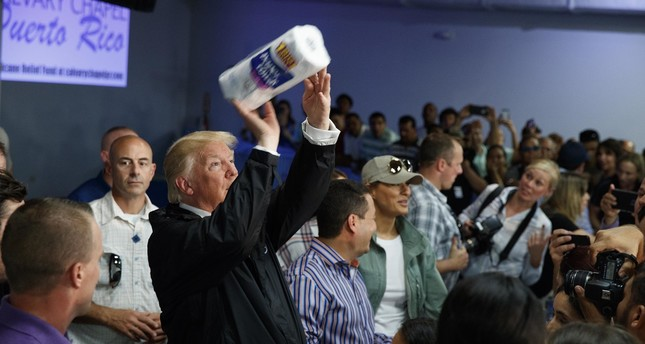 President Donald Trump tosses paper towels into a crowd as he hands out supplies at Calvary Chapel, Tuesday, Oct. 3, 2017, in Guaynabo, Puerto Rico. (AP Photo)