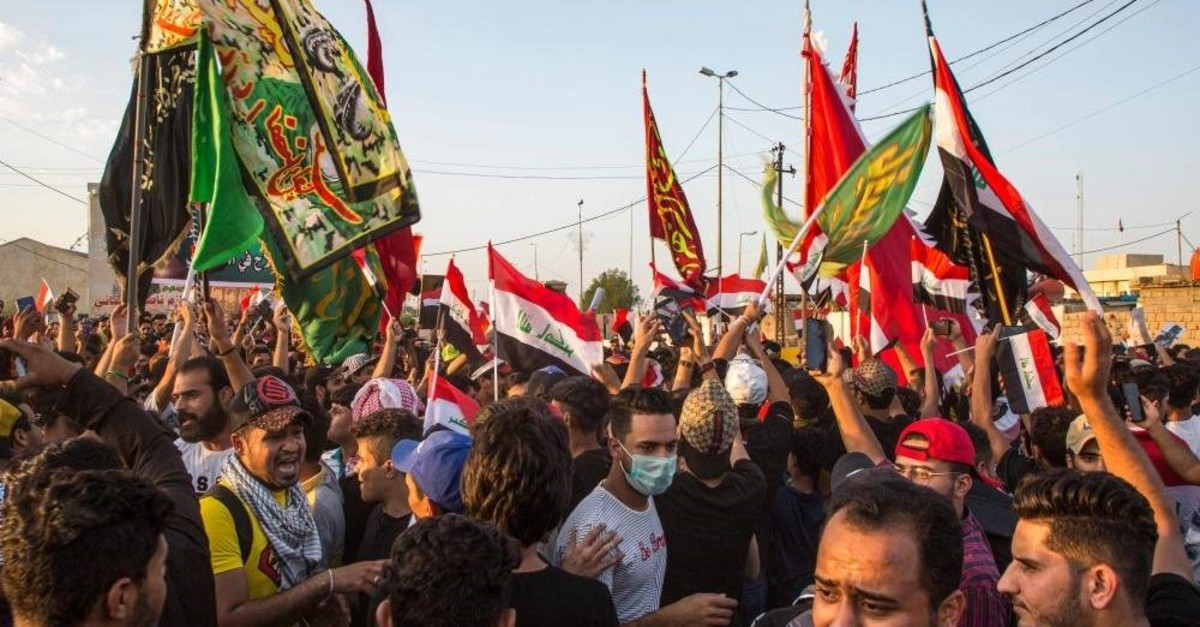 Iraqi protesters raise national and religious Shiite flags as they gather during an anti-government demonstration, Basra, Oct. 29, 2019. (AFP Photo)