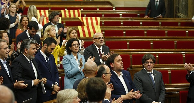 Catalonia regional President Carles Puigdemont, right, stands with others parliamentarians on their seats, after the voting during a plenary session at the Parliament of Catalonia in Barcelona, Spain, Wednesday, Sept. 6, 2017 (AP Photo)