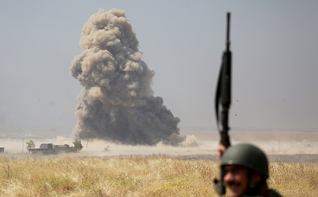 A Kurdish peshmerga member celebrates as smoke rises from a Daesh target hit during Coalition airstrikes. (AA Photo)
