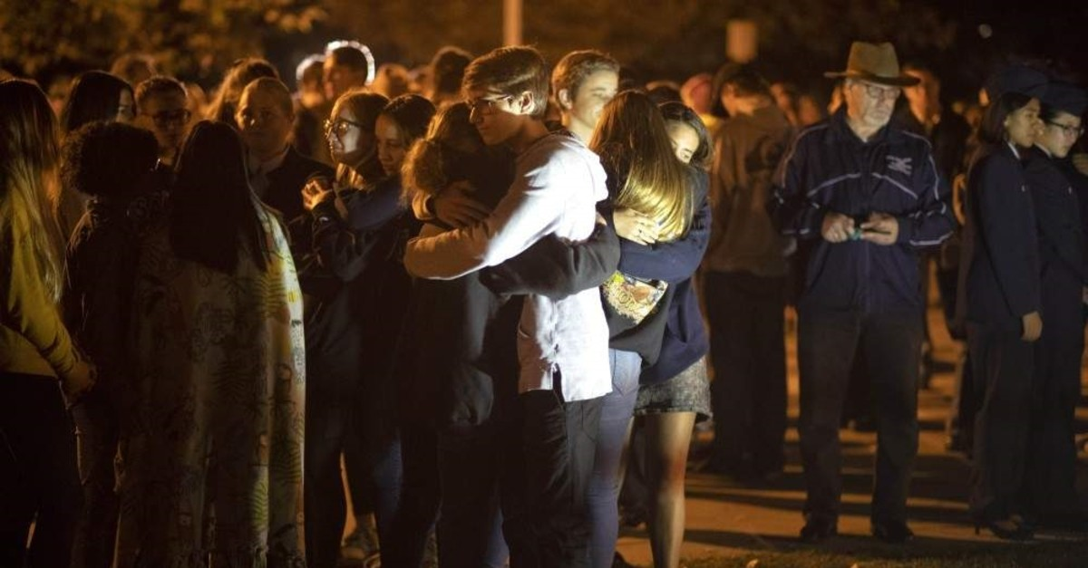 People affected by the Saugus High School shooting comfort each other during a vigil at Central Park in Santa Clarita, California, Thursday, Nov. 14, 2019. (Hans Gutknecht/The Orange County Register via AP)