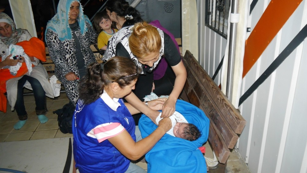 A migration official checks an infant among rescued migrants.