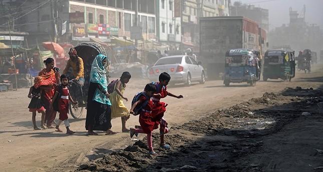 Schoolchildren cross a dusty road in Dhaka, Bangladesh March 4, 2018. (Reuters Photo)