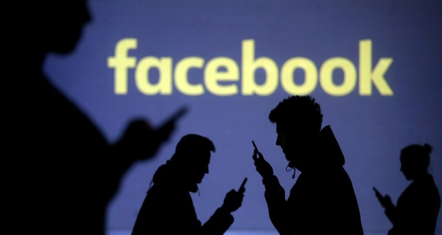 Silhouettes of mobile users are seen next to a screen projection of the Facebook logo in this picture illustration taken March 28, 2018 (Reuters File Photo)