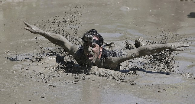 A participant swims to cross a mud pool during the Mud Day athletic event at El Goloso Military base on the outskirts of Madrid, Spain, Saturday, June 11, 2016. AP Photo