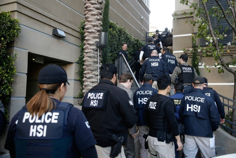In this March 3, 2015 file photo, federal agents enter an upscale apartment complex where authorities say a birth tourism business charged pregnant women $50,000 for lodging, food and transportation, in Irvine, Calif. (AP Photo)