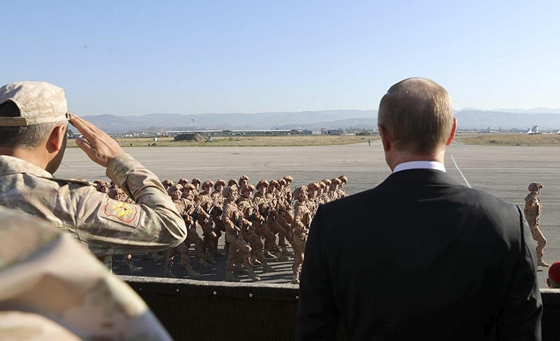 In this file photo taken on Tuesday, Dec. 12, 2017, Russian President Vladimir Putin, right, watches the troops marching as he and Syrian President Bashar Assad visit the Hemeimeem air base in Syria. (AFP Photo)